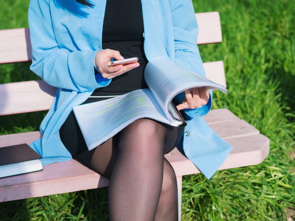 business-woman-using-her-mobile-device-while-sitting-on-the-bench-in-park-at-spring-and-reading_t20_9JYWRO